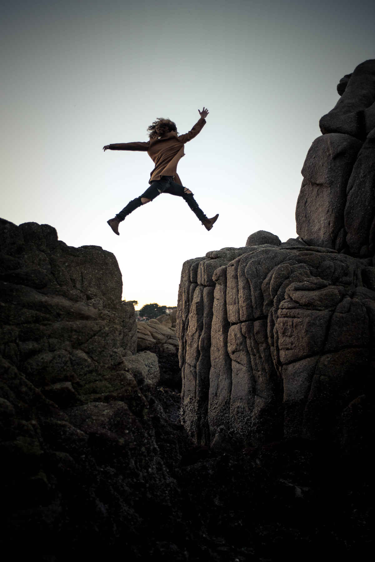 woman jumping over a cliff taking risk