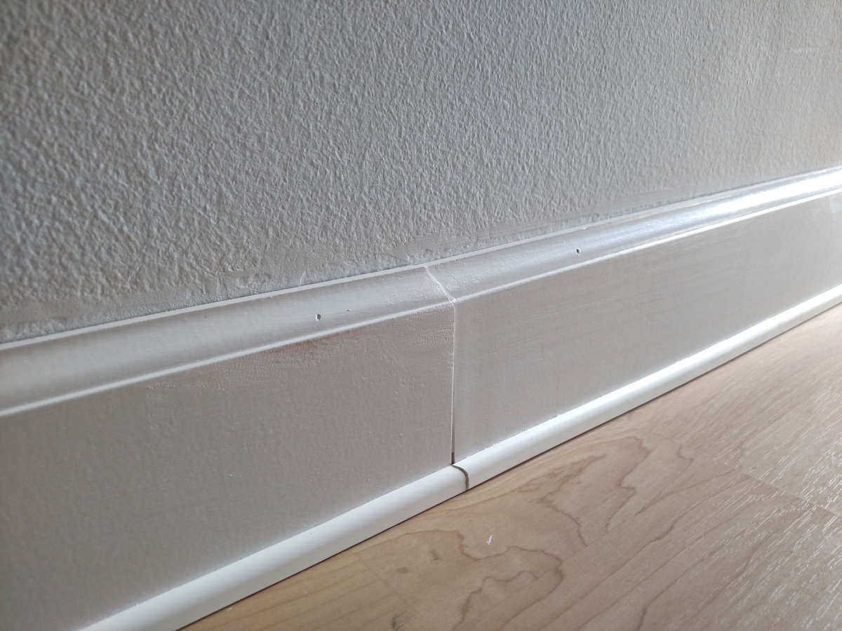 Baseboard joint showing how building movement causes misalignment of materials.