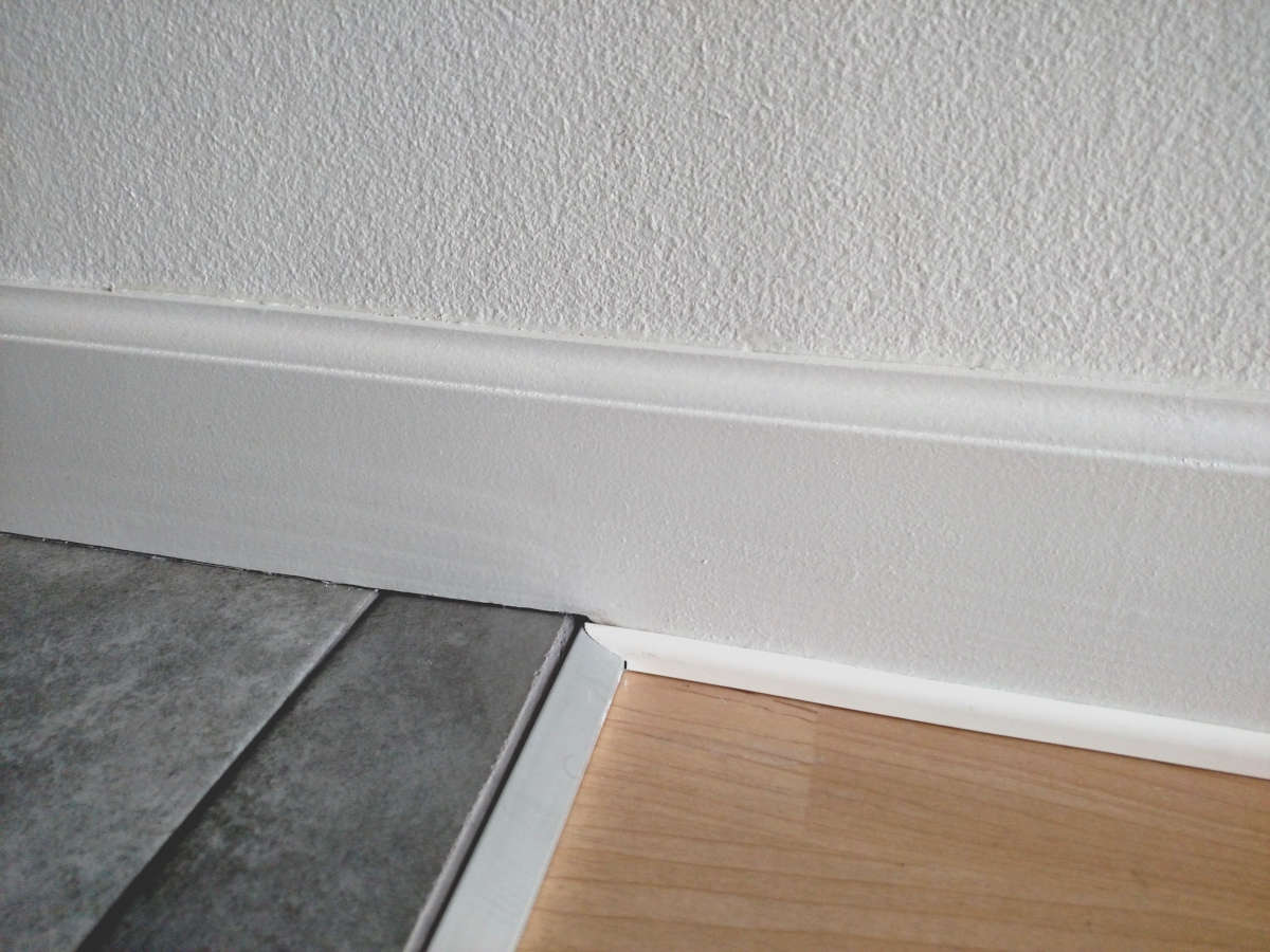 Baseboard transition to tile with a modified shoe piece cut to match aluminum transition strip.