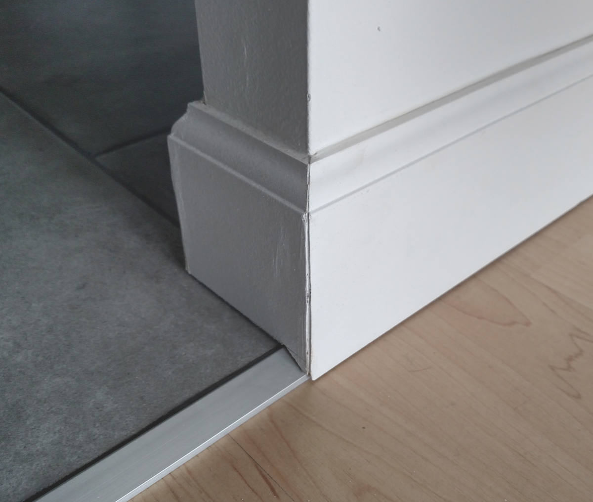 Baseboard corner condition with transition to tile.